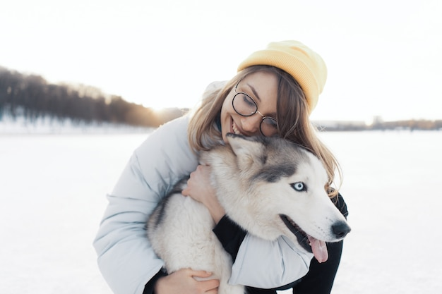Happy young girl playing with siberian husky dog in winter park