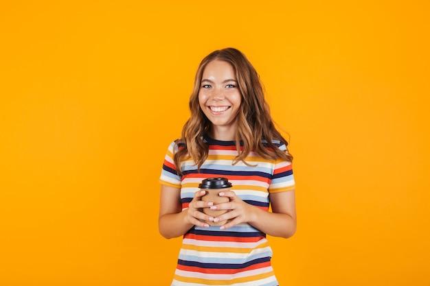 Счастливая маленькая девочка позирует над желтой стеной, пить кофе.