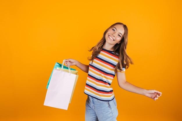 Счастливая маленькая девочка позирует над желтым стенным пространством, держащим хозяйственные сумки.