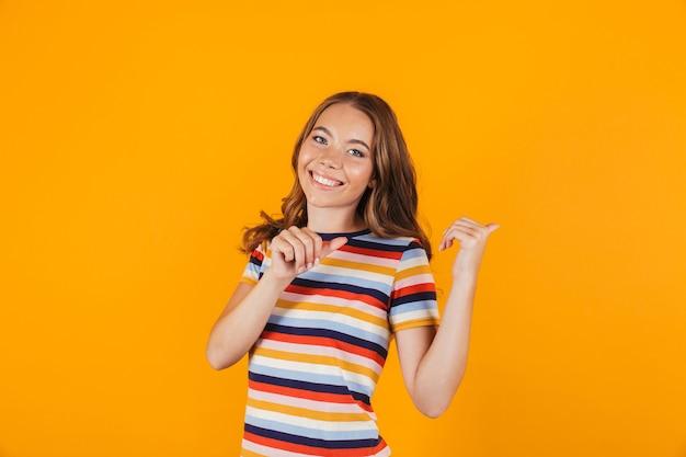 Счастливая маленькая девочка позирует над желтой стеной указывать пространство.