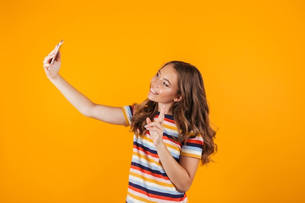 Счастливая молодая девушка позирует над желтым стенным пространством, делает селфи по мобильному телефону.