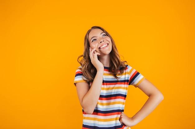 Счастливая молодая девушка позирует над желтой стеной, разговаривает по телефону.