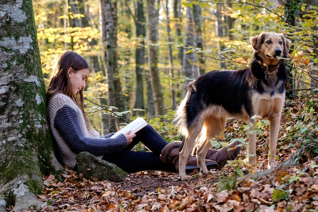 Happy young girl reading a book with her dog in autumn forest