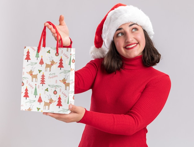 Felice giovane ragazza in maglione rosso e cappello santa tenendo il sacchetto di carta colorato con i regali di natale che guarda da parte con il sorriso sul viso in piedi su sfondo bianco