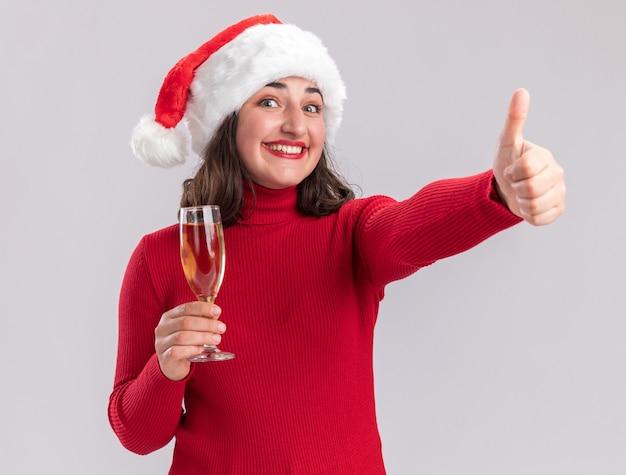 Felice giovane ragazza in maglione rosso e santa hat tenendo un bicchiere di champagne guardando la fotocamera con il sorriso sul viso che mostra i pollici in su in piedi su sfondo bianco