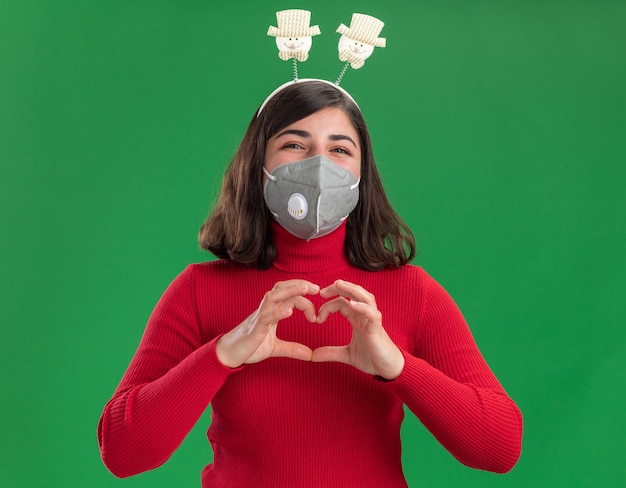 Happy young girl in red sweater with funny headband wearing facial protective mask making heart gesture with fingers  standing over green wall