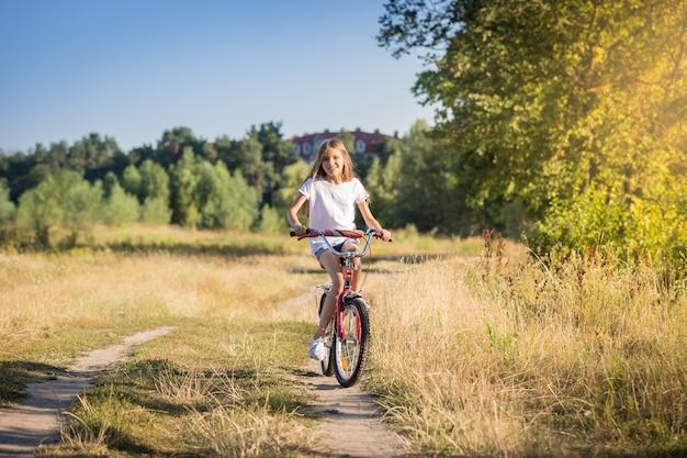 화창한 날 초원에서 자전거를 타는 행복한 어린 소녀