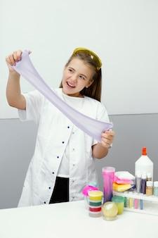 점액을 만드는 행복 한 어린 소녀 과학자