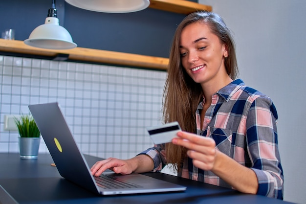 幸せな若い女の子の買い物客はオンラインで買い物をし、クレジットカードとラップトップを使用して商品や購入の支払いをします。 eコマース