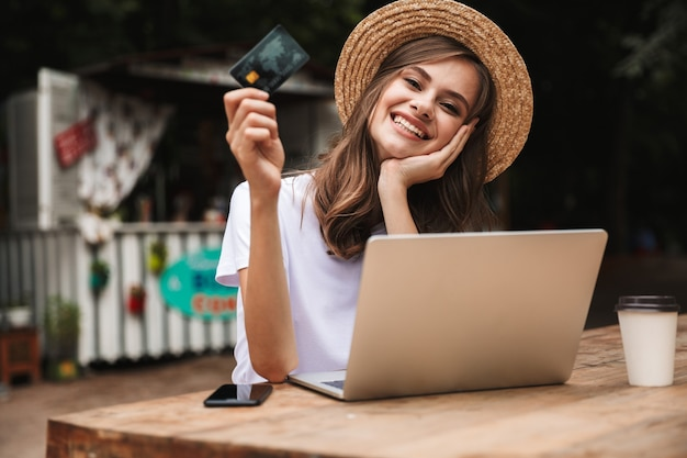 Happy young girl showing plastic credit card while sitting with laptop computer and coffee at the cafe outdoors
