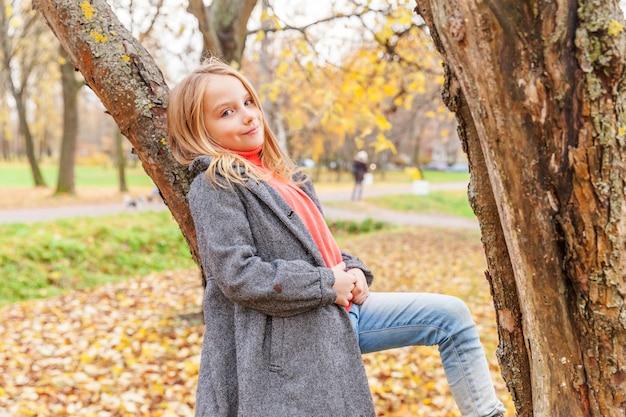 행복 한 어린 소녀 웃 고 자연에 아름 다운가 공원에서 나무에 앉아 야외 산책. 가을 주황색 노란색 배경에서 노는 어린 아이. 안녕하세요 가을 컨셉입니다.