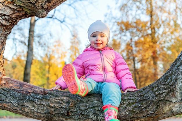 행복 한 어린 소녀 웃 고 자연에 아름 다운가 공원에서 나무에 앉아 야외 산책. 가을 오렌지 노란색 배경에서 노는 어린 아이. 안녕하세요 가을 컨셉입니다.