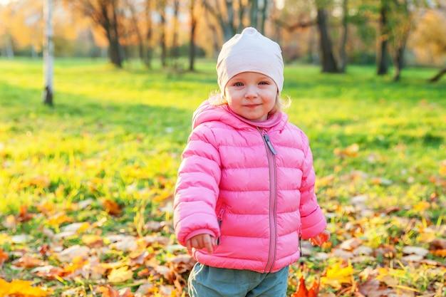 자연의 아름다운 가을 공원에서 웃고 있는 행복한 어린 소녀가 야외에서 산책합니다. 가을 오렌지 노란색 배경에서 노는 어린 아이. 안녕하세요 가을 컨셉입니다.