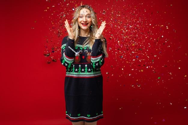 Ragazza felice in coriandoli scintillanti per celebrare il nuovo anno e il natale