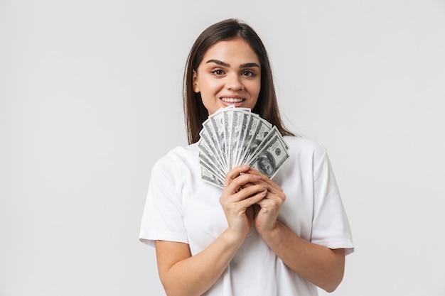 Счастливая молодая девушка, стоящая изолирована на белом, показывая денежные банкноты