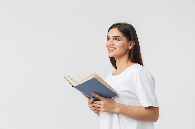 Happy young girl standing isolated on white, reading a book