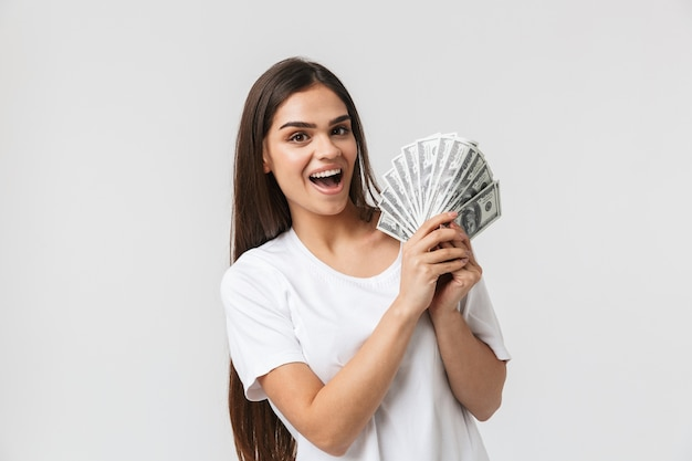 Happy young girl standing isolated on white, showing money banknotes