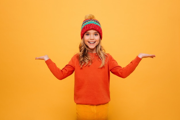 Happy young girl in sweater and hat shrugs her shoulders while looking at the camera over orange
