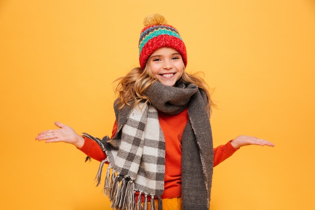 Happy young girl in sweater, scarf and hat shrugs her shoulders while looking at the camera