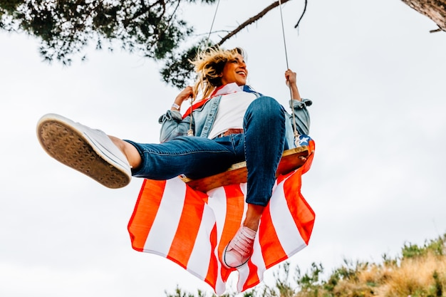 Happy young girl swinging with an american flag.