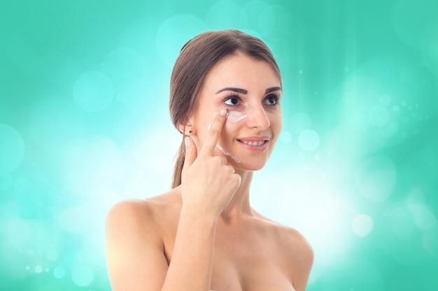 Счастливая молодая девушка заботится о своей коже, изолированной на белом фоне. концепция здравоохранения. концепция ухода за телом. молодая женщина со здоровой кожей.