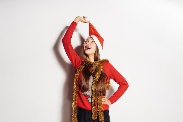 幸せな若い女の子は彼の頭からサンタクロースのような赤い帽子を脱いで、新年とクリスマスを待っています