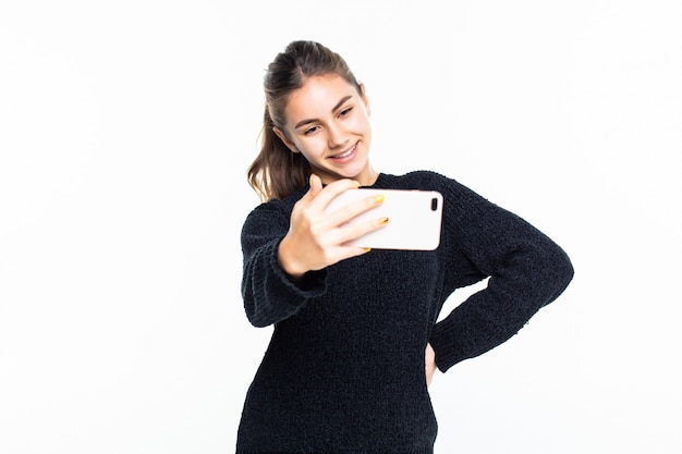 Happy young girl taking pictures of herself through cell phone over white wall