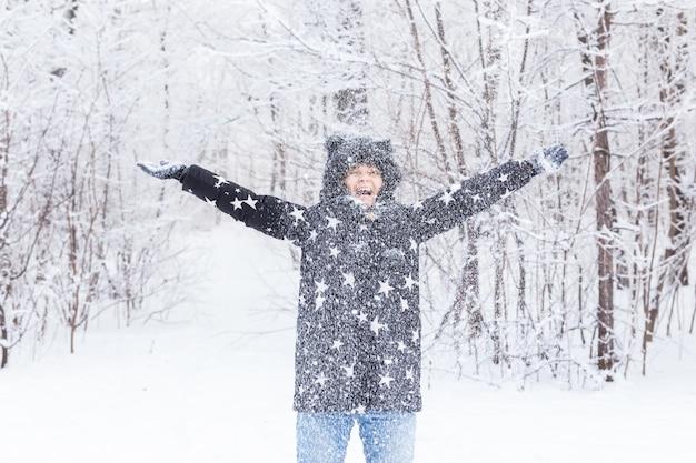 행복 한 어린 소녀 겨울 숲에서 눈을 던졌습니다