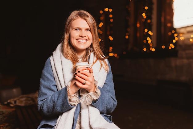 Счастливая молодая девушка взяла кофе, чтобы пойти, улыбается в камеру.