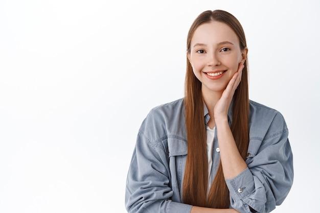 Ragazza felice che si tocca il viso, sorride compiaciuta, mostra una pelle del viso liscia e delicata, in piedi contro il muro bianco con una camicia fresca.