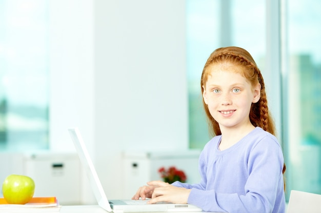 Happy young girl using laptop