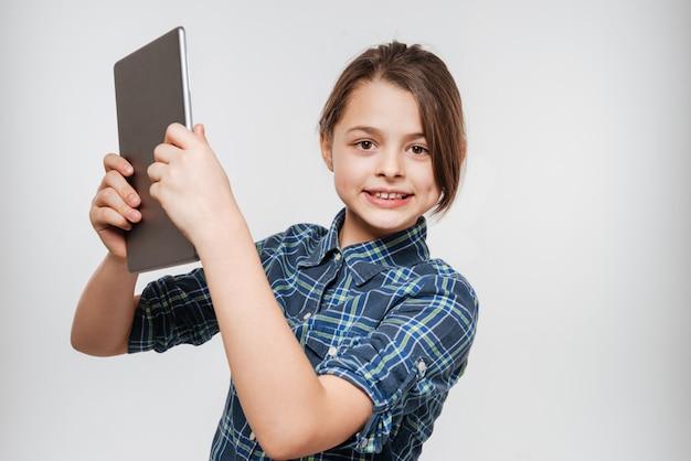 タブレットコンピューターを使用して幸せな若い女の子