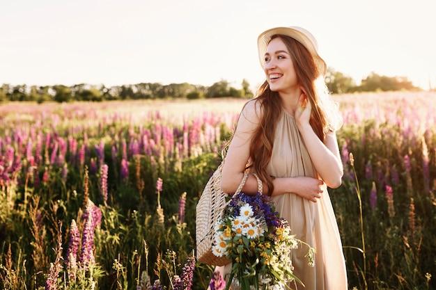 Счастливый молодая девушка, ходить в поле цветов на закате. ношение соломенной шляпы и сумка с цветами.