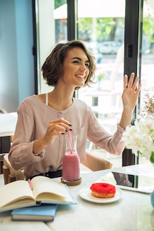 Happy young girl waving hand while drinking smoothie