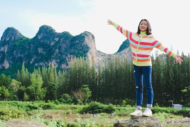 Счастливая молодая девушка носить свитер стоя с красивым пейзажным видом.