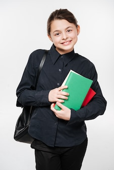 Happy young girl wearing backpack holding books