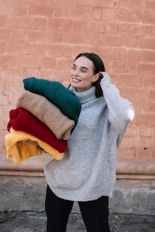 Happy young girl wearing a knitted grey sweater is smiling and looking aside while holding colourful blankets