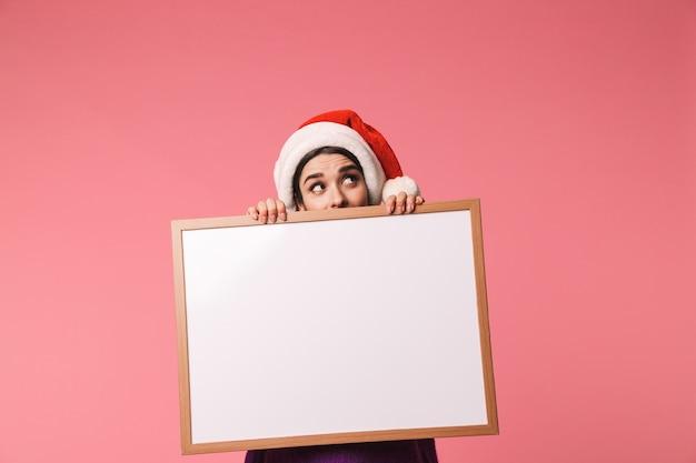 빈 보드를 보여주는 핑크 이상 격리 서 빨간 산타 모자를 쓰고 행복 한 어린 소녀