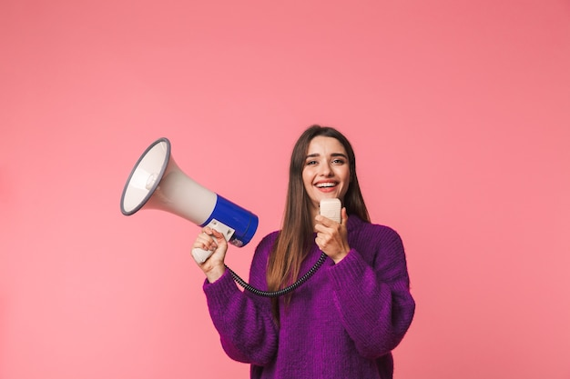 Happy young girl wearing sweater standing isolated over pink, shouting in a speaker