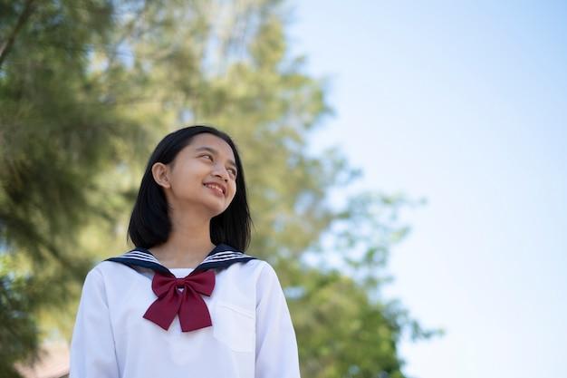 幸せな若い女の子は学校で学生のunformを着ています