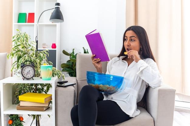 Felice ragazza in camicia bianca e pantaloni neri con una ciotola di patatine che tiene in mano un libro che legge e mangia seduta sulla sedia in un soggiorno luminoso