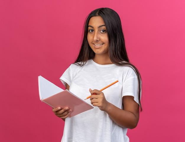 Ragazza felice in maglietta bianca che tiene taccuino e matita che guarda l'obbiettivo con un sorriso sul viso in piedi sopra il rosa