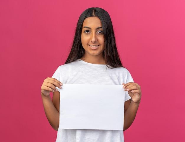 Felice ragazza con una maglietta bianca che tiene un foglio di carta bianco bianco che guarda la telecamera sorridendo allegramente
