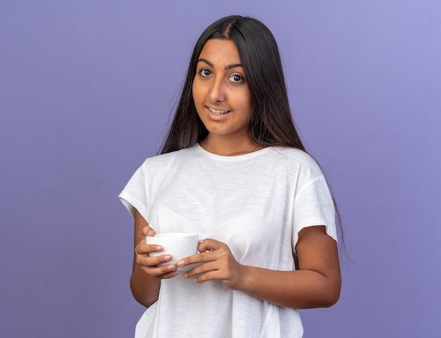 Felice ragazza con una maglietta bianca che tiene in mano una tazza bianca che guarda la telecamera sorridendo allegramente in piedi sopra il blu