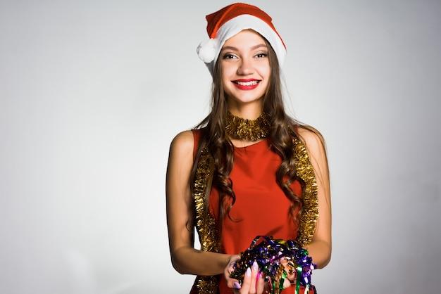 Счастливая молодая девушка с красной шапочкой на голове, на шее из мишуры, встречает новый год