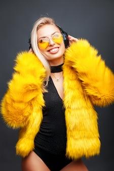 Счастливая молодая девушка с улыбкой слушает музыку в модных желтых солнцезащитных очках и стильной желтой шубе на сером