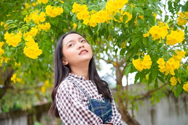 美しい黄色い花を持つ幸せな少女。