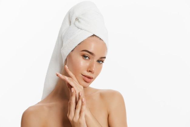Happy young girl with clean skin and with a white towel on her head washes face.
