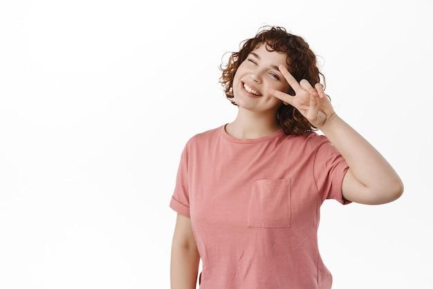 巻き毛、ウインクと笑顔で幸せな若い女の子vサイン、目の近くにポジティブなカワイイジェスチャー、白で明るい立っている
