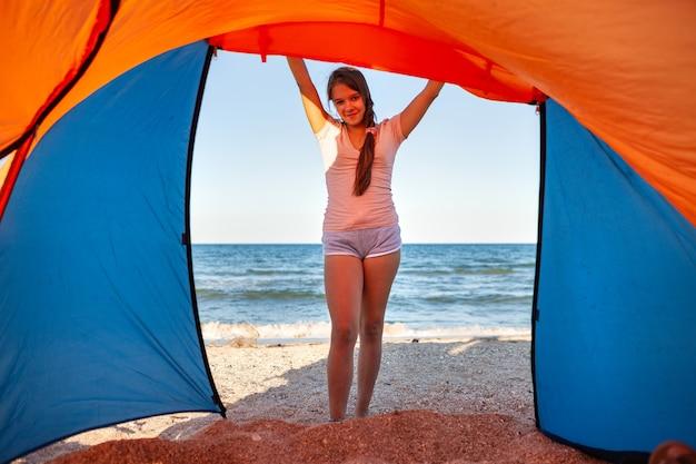 검은 머리와 함께 행복 한 어린 소녀는 푸른 바다의 모래 사장에 밝은 텐트 미소 근처에 서